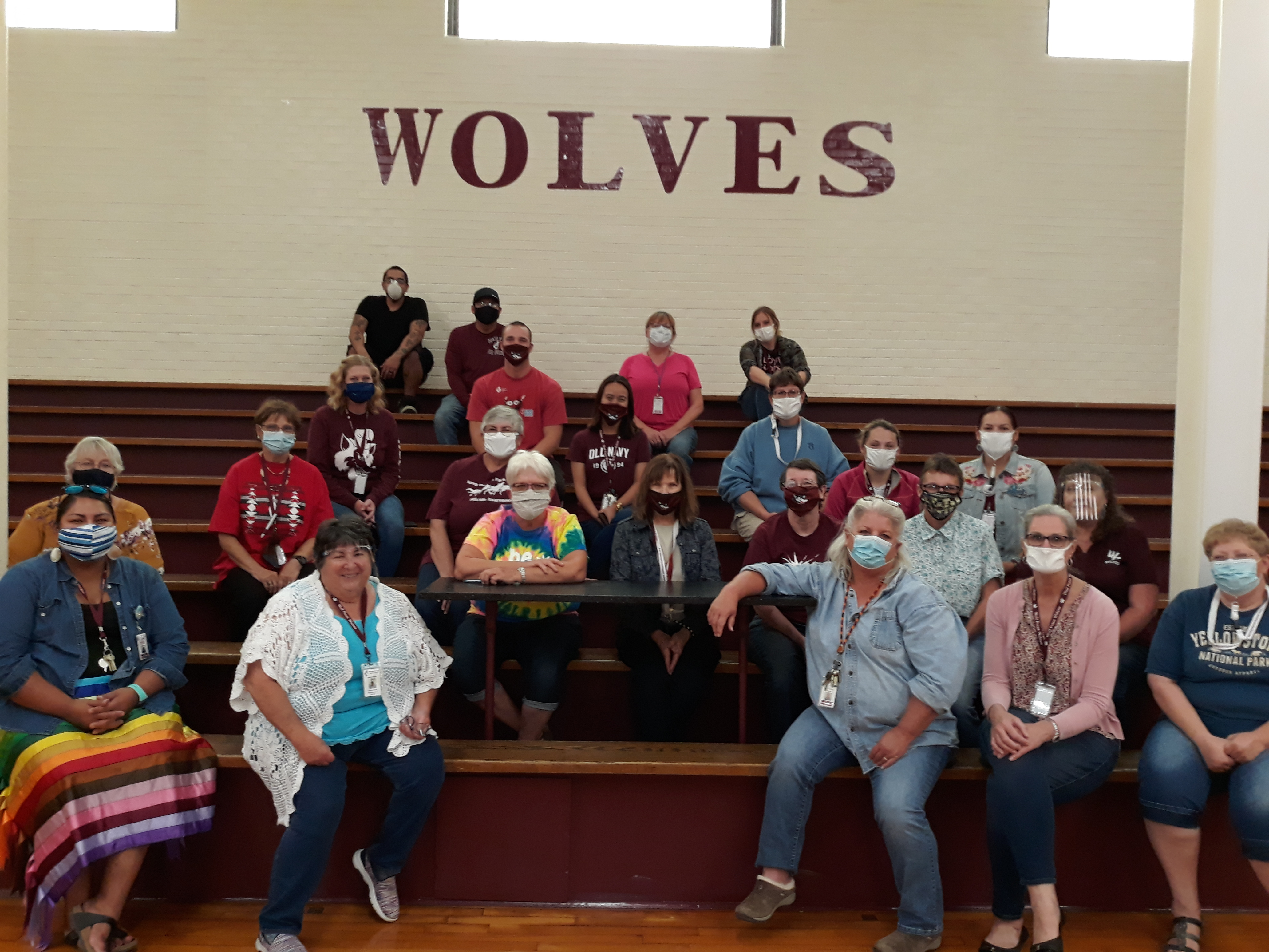 Staff of Southside Elementary wearing masks and sitting on bleachers